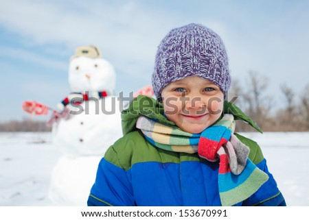 Portrait of cute boy with snowman outside in winter time - stock photo