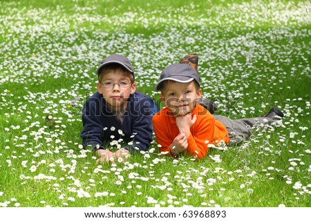 Portrait of cute brothers lying on green grass and looking at camera - stock photo