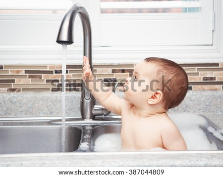 Portrait of cute Caucasian funny baby girl boy with dark black eyes sitting in big kitchen sink playing with water and foam near window looking away, lifestyle everyday concept - stock photo