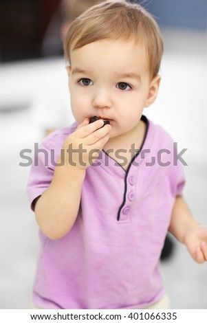 Portrait of cute cheerful boy eating candy - stock photo