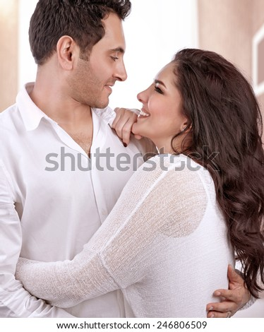Portrait of cute cheerful family at home, beautiful woman and handsome man hugging and looking on each other with love - stock photo