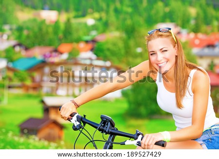 Portrait of cute cheerful girl enjoying bicycle tour along villages in Alpine mountains, active lifestyle, sportive summer vacation - stock photo