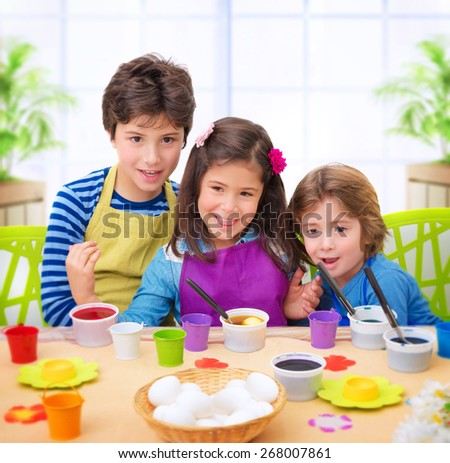 Portrait of cute cheerful kids paint eggs at home, happy Easter tradition, celebrating christian holiday with pleasure, makes festive decoration - stock photo