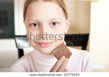 Portrait of cute cheerful little girl with piece of chocolate. - stock photo
