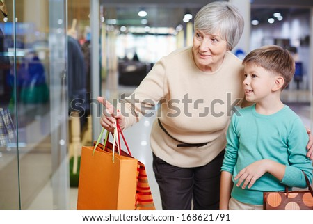 Portrait of cute child and his grandmother with paperbags looking at shop window - stock photo