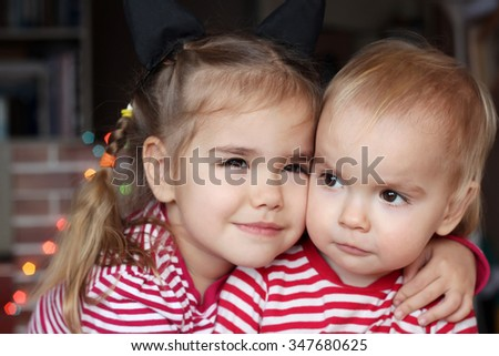 Portrait of cute child girl hugging a toddler boy over Christmas background, winter holiday family concept - stock photo
