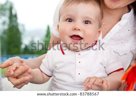 Portrait of cute child holding mother's hand - stock photo