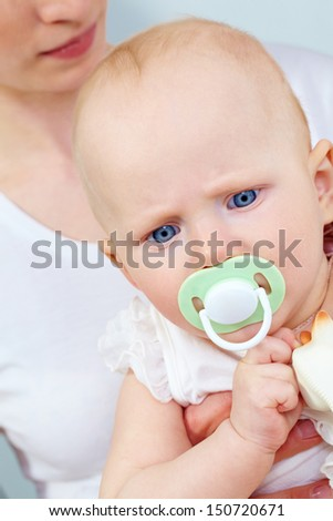 Portrait of cute child with pacifier in mouth held by her mother - stock photo