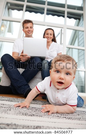 Portrait of cute child with parents using laptop in the background - stock photo