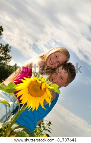 Portrait of cute children looking at camera and smiling in sunflower field - stock photo