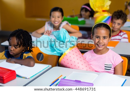 Portrait of cute children with craft work sitting on bench in classroom