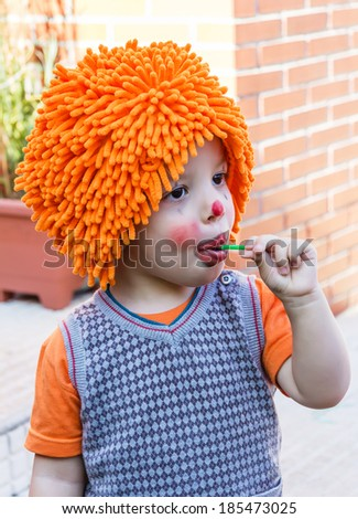Portrait of cute clown child eating lollipop in a party - stock photo