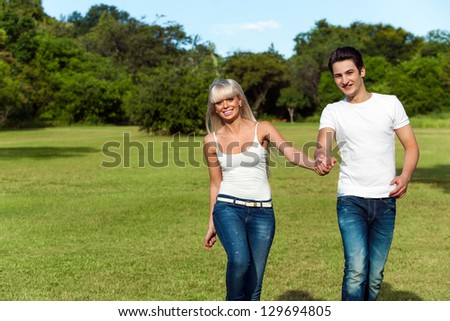 Portrait of cute couple doing hop skip and jump in park. - stock photo