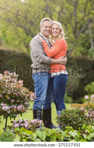 Portrait of cute couple hugging in the garden - stock photo