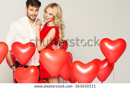 Portrait of cute couple with balloons heart - stock photo