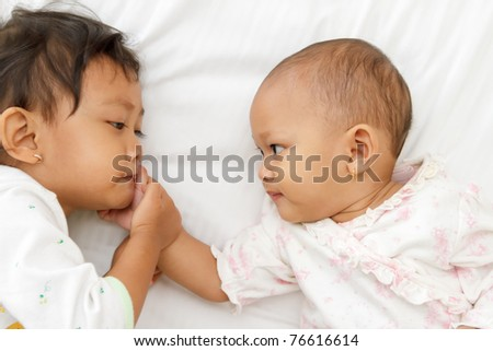 portrait of cute ethnic little girl playing with baby in bed