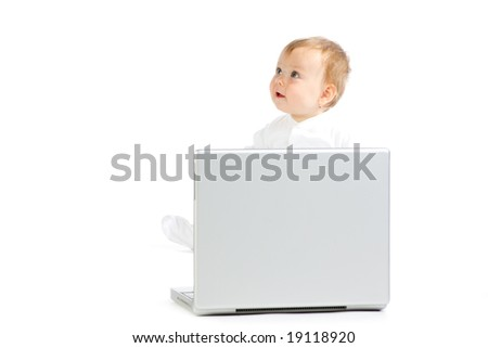 Portrait of cute female baby sat by side of laptop computer, isolated on white background. - stock photo