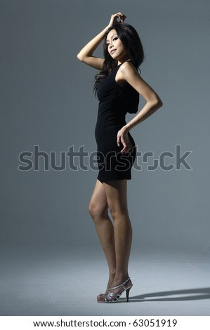 Portrait of cute female fashion model posing on light background - stock photo