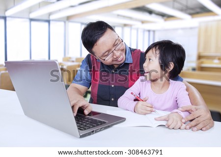 Portrait of cute female student studying and talking with her teacher in the classroom while using a book and laptop - stock photo