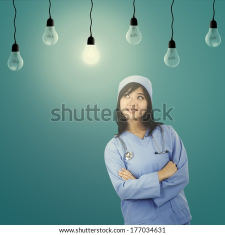 Portrait of cute female surgeon looking at light bulb - stock photo