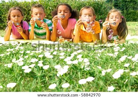 Portrait of cute friends having bubble fun on green lawn in park - stock photo