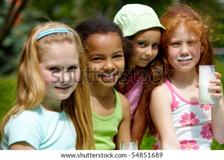 Portrait of cute friends looking at camera while relaxing outside - stock photo