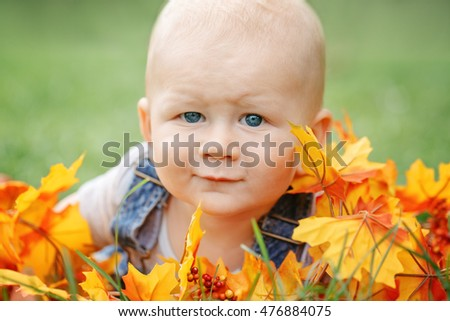 Portrait of cute funny adorable blond Caucasian baby boy with blue eyes in tshirt and jeans romper lying on grass field meadow, yellow autumn fall leaves. Halloween, Thanksgiving.