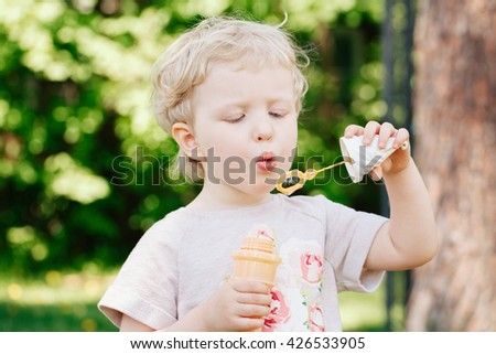 Portrait of cute funny little blond Caucasian child girl toddler standing in the green forest field meadow blowing soap bubbles, bright summer day, summer fun