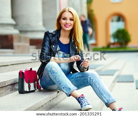 portrait of cute funny modern sexy urban young stylish smiling woman girl model in bright modern cloth outdoors sitting in the city  in jeans with pink bag - stock photo