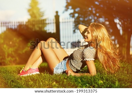 portrait of cute funny sexy young stylish smiling woman girl model in bright modern cloth with perfect sunbathed body outdoors lying in the park in jeans shorts holding healthy strong hair in hand - stock photo