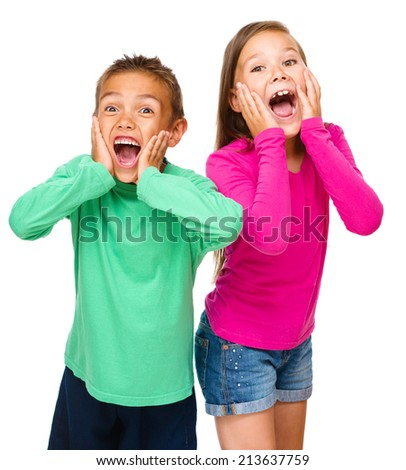 Portrait of cute girl and boy holding their faces in astonishment, isolated over white - stock photo