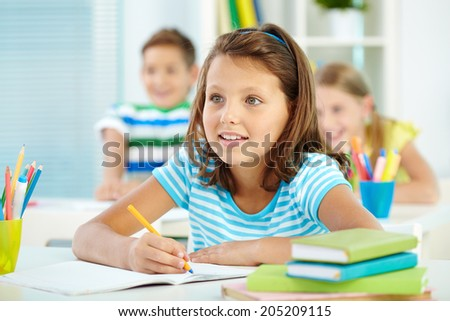 Portrait of cute girl and her two schoolmates on background looking at something attentively at lesson - stock photo
