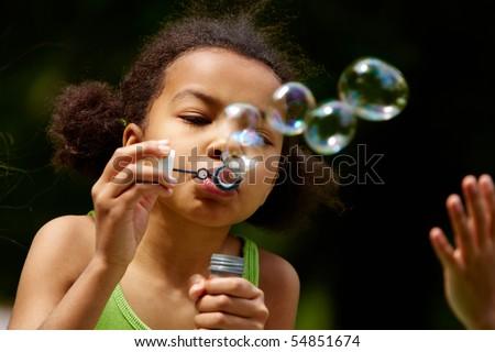 Portrait of cute girl blowing soap bubbles - stock photo