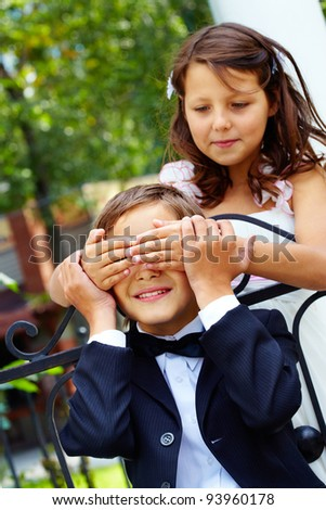 Portrait of cute girl bride shutting eyes of her groom by hands - stock photo