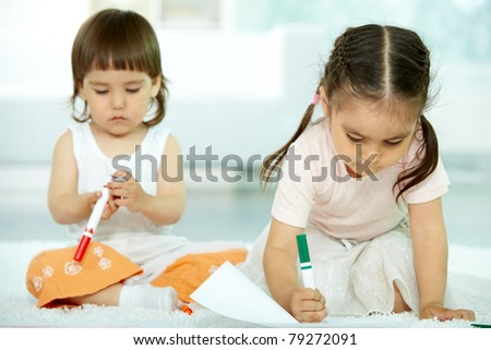 Portrait of cute girl drawing  with highlighter on background of her sister - stock photo