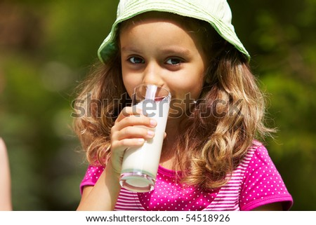 Portrait of cute girl drinking kefir outdoors - stock photo