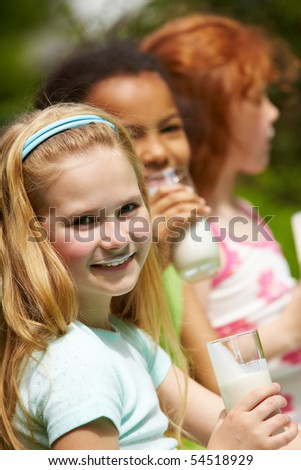 Portrait of cute girl drinking kefir outdoors with her friends on background - stock photo