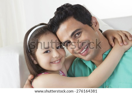 Portrait of cute girl embracing father in house - stock photo