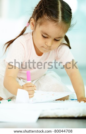 Portrait of cute girl holding highlighter and drawing - stock photo