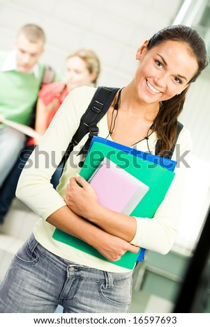 Portrait of cute girl holding textbook in hands on background of reading students