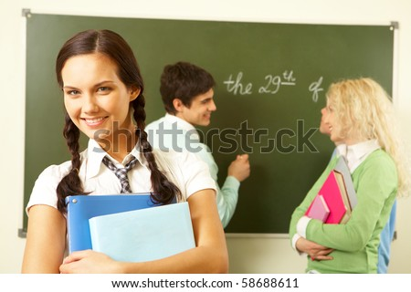 Portrait of cute girl holding textbooks in hands on background of communicating groupmates - stock photo