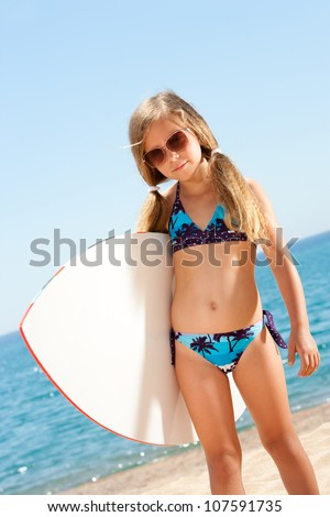 Portrait of cute girl in bikini holding white surfboard on beach.