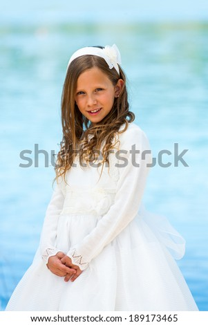 Portrait of cute girl in communion dress with water background. - stock photo