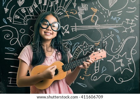 Portrait of cute girl in eyeglasses playing guitar by the blackboard with chalk drawings of musical instruments. - stock photo