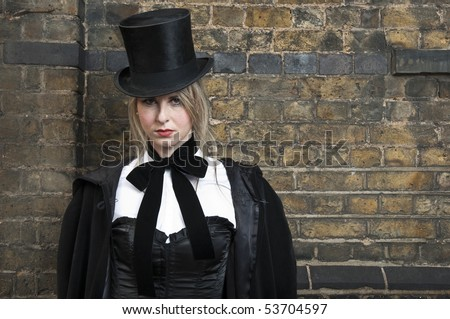 Portrait of cute girl in Victorian clothes against brick wall. - stock photo