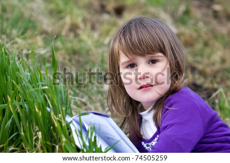 Portrait of cute girl laying on grass and reading interesting book