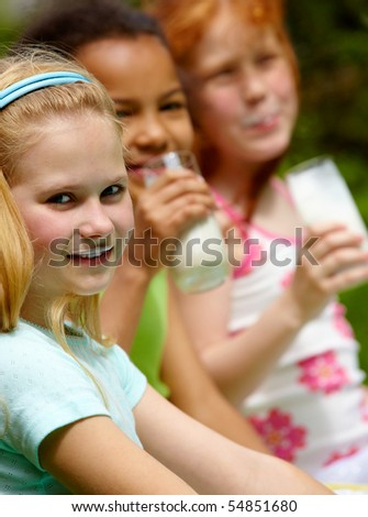 Portrait of cute girl looking at camera with her friends drinking kefir on background