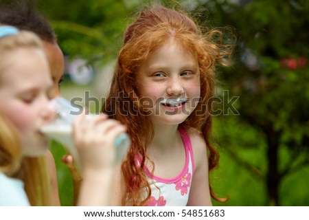 Portrait of cute girl looking at friends drinking kefir near by - stock photo