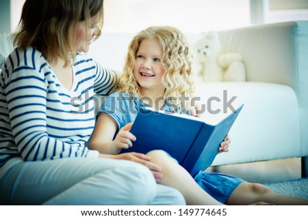 Portrait of cute girl looking at her mother while discussion of an interesting story at home - stock photo