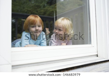 Portrait of cute girl lying with sister in front of glass window at home